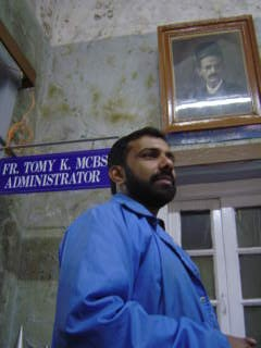 Father Tomy in front of a picture of Dr Billimoria, the founder of the Bel-Air Hospital